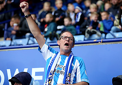 A Huddersfield Town fan cheers from the stands during the Premier League match at the King Power Stadium, Leicester.
