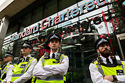 With police in the foreground, climate activists from Extinction Rebellion covers the signage for the Standard Chartered building with red paint, signifying fake blood, on 27th August, 2021 in London, United Kingdom. The activist group Extinction Rebellion XR are planning actions of disruption for two weeks straight beginning on August 23rd, 2021 in an effort to bring awareness and priority to the global climate emergency in advance of the COP 26 Summit which will be held in Glasgow later this year.