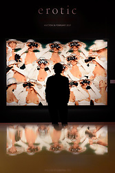 "© Licensed to London News Pictures. 10/02/2017. London, UK.  A man is silhouetted against ""Ascot"" by Gunter Sachs (est. GBP8-12k), at the preview of the ""Erotic: Passion & Desire"" sale at Sotheby's in New Bond Street.  The sale, which will take place on 16 February, encompasses representations of love and sex from antiquity to the present day.  Photo credit : Stephen Chung/LNP"