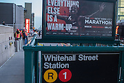 "A sign advertising the New York City Marathon, cancelled because of the storm, ironically states ""Everything else is a warm-up."" MTA workers in safety vests can be seen in the distance, beyond the still closed Whitehall Street subway station."