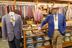Salesman in suit section at M.L Leddy's Boots, Fort Worth Stockyards National Historic District, Fort Worth, Texas, USA.