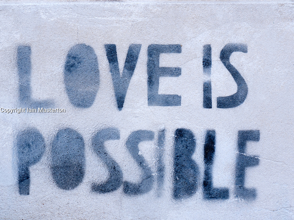 Detail of graffiti painted on wall with message Love is Possible in bohemian district of Prenzlauer Berg in Berlin Germany