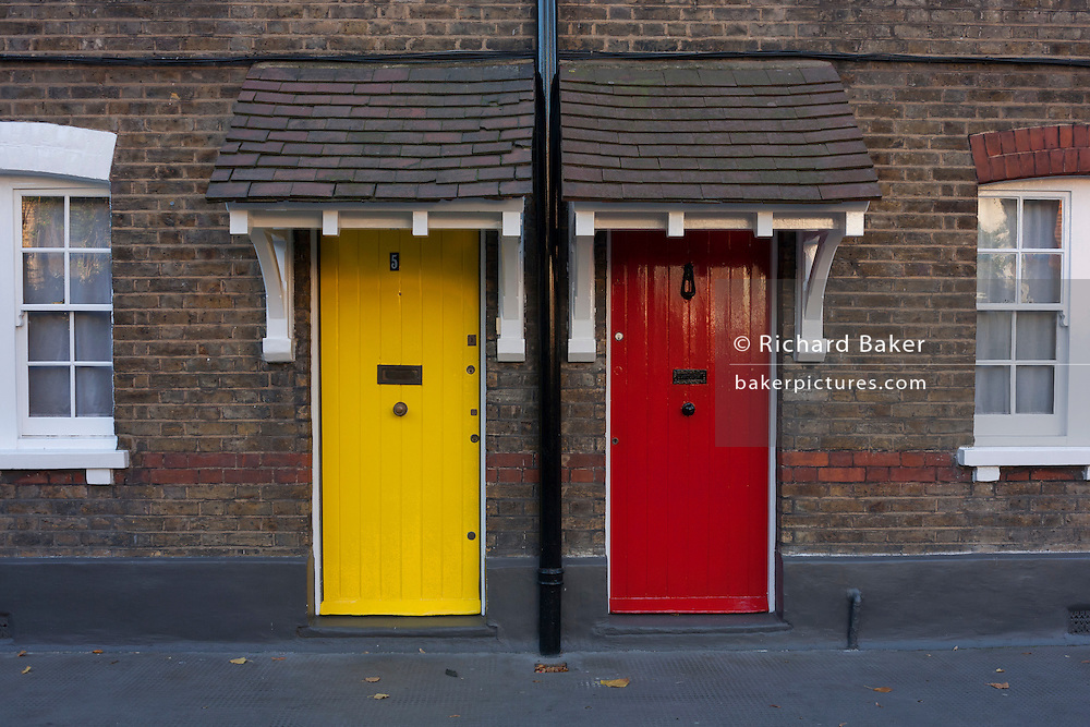 Neighbours' doors of Winchester Cottages on Copperfield Street, on 28th November 2016, in the south London borough of Southwark, England.