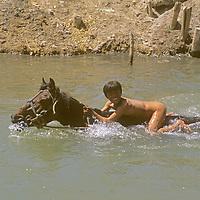 A Uygar boy rides naked and bareback to test ride horses at the Sunday Market in Kashgar (Kashi), Xinjiang, China.