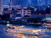 23 MARCH 2016 - BANGKOK, THAILAND: Chao Phraya Princess Cruise III on the Chao Phraya River in Bangkok at sunset. The ship, which takes tourists on dinner cruises, was built in 2005. It is 11 meters wide, 53 meters long and weighs 469 tons. It can hold 350 passengers.  PHOTO BY JACK KURTZ