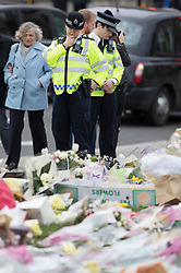 © Licensed to London News Pictures. 29/03/2017.London, UK. Police look at floral tributes placed in Parliament Square one week after the Westminster Bridge attack on 22nd March 2017 in which three people were run down by a car driven by Khalid Masood just before he stabbed policeman Keith Palmer at the entrance to Parliament.Photo credit: Peter Macdiarmid/LNP