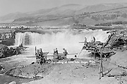 9305-B7372. Indians fishing at Celilo Falls, September 1938. The cablecar line in the foreground was for a hand operated car that went from this spot on the Oregon riverbank to Chinook rock, which can be seen on the extreme left. Within two years this was replaced by a footbridge that would be reconstructed every year. This was the area that was most accessible to tourists, who were constantly walking around therocks buying fish and the low-hanging cable line was a hazard.