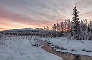 Alpenglow sunrise surrounds the Chugach Mountains in Southcentral Alaska. Winter.