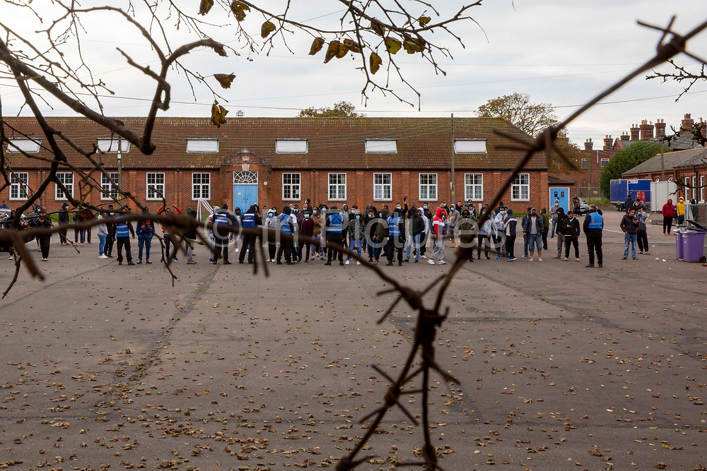 Refugees inside the barracks came out into the yard to enjoy the locals 'Welcome To Folkestone' event from local residents and community groups including Kent Refugee Action Network and Samphire came together outside Napier Barracks to show the people staying there that they are welcome to the town on the 17th of October 2020 in Folkestone, United Kingdom. In September 2020 Napier Barracks a former military camp was transformed into an assessment and dispersal facility for 400 asylum seekers by the Home Office.