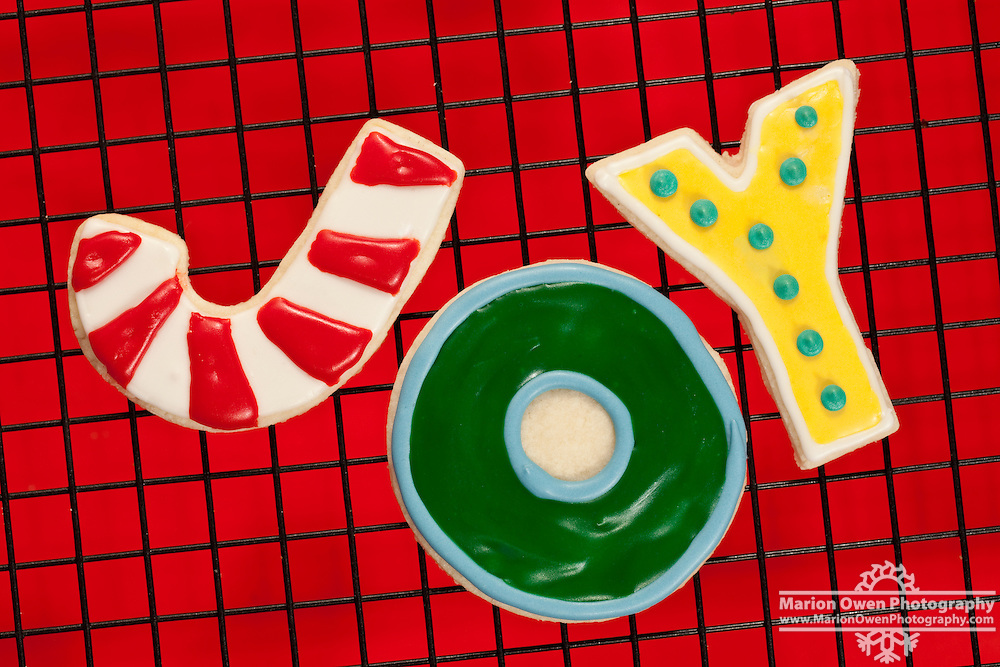 Closeup of Christmas sugar cookies spelling J-O-Y arranged on black mesh cooling rack over red tablecloth.
