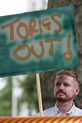 A man holds a sign reading Tories Out at a protest opposite Downing Street by leaseholders and tenants living in unsafe homes on 15th July 2021 in London, United Kingdom. Some leaseholders are faced with crippling costs to fix safety issues and they called on the government to ensure that their homes are made safe from fire as a matter of priority, to make interim payments and to cover fire safety remediation costs and to find a solution with mortgage lenders which enables them to move on with their lives.