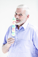 caucasian senior man portrait eating candy isolated studio on white background