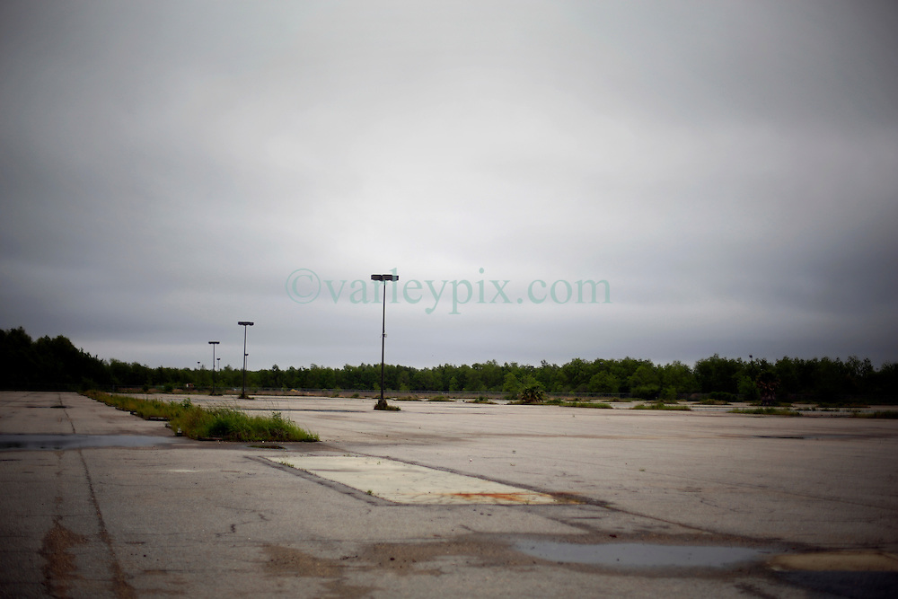 15 April 2016. New Orleans, Louisiana.<br /> Abandoned Six Flags amusement park in New Orleans East.<br /> Not amusing any more. Empty parking lot.<br /> 'Closed for storm.' Six Flags former amusement park radiates an eerie post apocalyptic sense of foreboding in it's abandonment. The park was destroyed by hurricane Katrina in August 2005, stripped by copper thieves and is slowly being reclaimed by the land it stands on. The site is now home to thriving wildlife. Would be developers for the former Jazzland site have proposed various ideas over the years to revive the area into a theme park and shopping complex, proposals which have been rejected by the Industrial Development Board. <br /> Photo; Charlie Varley/varleypix.com