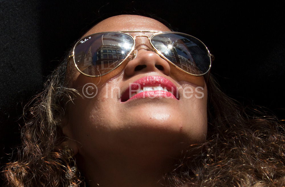 """London, UK. Wednesday 4th September 2013. American in London Beverly looks up as the beam of light reflecting off the Walkie Talkie in turn reflects off her mirrored sunglasses. Urgent action in planned to """"cover up"""" the Walkie Talkie skyscraper in the City after sunlight reflected from the building melted a car on the streets below. Temperatures have been measured in excess of 50 degrees C, and as much as 70 degrees at it's peak. The 525ft building has been renamed the """"Walkie Scorchie"""" after its distinctive concave surfaces reflected a dazzling beam of light which has caused extensive damage to nearby buildings."""