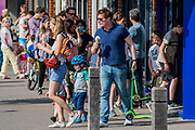 A large queue forms to buy ice cream at a gelataria on Northcote Road, Battersea/Clapham. They are social distancing (roughly 2m apart - as the lens comrpesses the view) but only until the doorway. It shows the dilema between keeping businesses going and 'Staying at Home' unless your journey is vital.