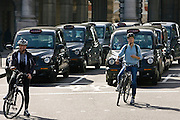 Two cyclists and black taxis in traffic waiting in Trafalgar Square, downtown London city centre, England, United Kingdom