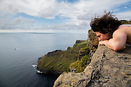 Visitor peering over the precipice along the Cliffs of Moher coastal walk