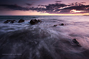 A pink sunset near Rhosneigr, West Anglesey. Gentle waves wrap around rocks just off the sandy beach and look soft because of motion blur.