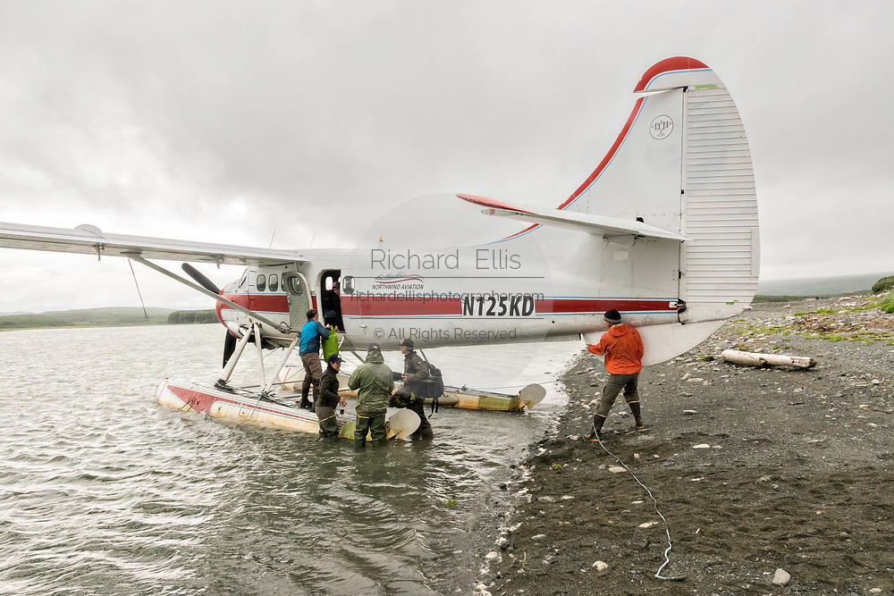 Passengers unload a de Havilland DHC-3 Otter seaplane after landing at the remote McNeil River Game Sanctuary in the Katmai Peninsula, Alaska. The float plane is the only way in and out of the remote location known for the highest concentration of brown bears in the world.