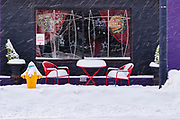 26 JANUARY 2021 - DES MOINES, IOWA: Outdoor seating at a restaurant in Des Moines after a heavy snowfall. Workers in Des Moines started cleaning up a record snowfall Tuesday morning. The National Weather Service reports that 10.3 inches of snow fell at Des Moines International Airport Monday, January 25, breaking the daily record of 10 inches for January 25 set in 1895. Many downtown businesses closed for the day because of the snow, since roads throughout central Iowa were snowpacked and hard to drive.       PHOTO BY JACK KURTZ