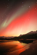 Alaska. Aurora borealis or northern lights. Hues of red. green and yellow above Knik River and Chugach Mts.