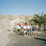 Gran Canaria, Spain. Norwegians leaving La Plaza Noruega after the annual Christmas service. La Plaza Noruega is a small, remote spot given to the Norwegian community by the local authorities. Here the Norwegians have planted a few palm trees and put up some tables and benches. The red hats are mandatory on this day.<br /> Photo by Knut Egil Wang/Moment/INSTITUTE