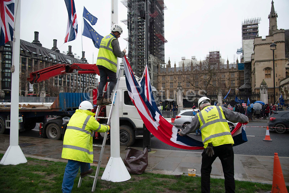 Workmen hoist the Union Jack flag up flag poles in preparation for Brexit outside the Houses of Parliament in Parliament Square, Westminster, on 30th January 2020, in London, England, United Kingdom. The United Kingdom will leave the European Union formally at 23:00 GMT on 31st January, 2020.