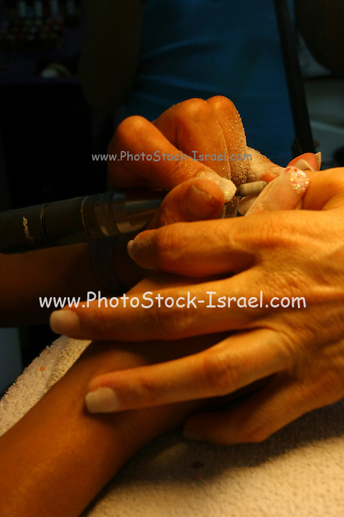 Manicurist takes care of womans fingernails, filing and smoothing after cutting