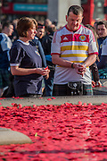 Scots fans, in town for tonights international against England, pause for thought at the poppy filled fountain - Silence in the Square oraganised by the British Legion in Trafalgar Square  - 11 November 2016, London.