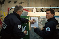 """© Licensed to London News Pictures . 23/10/2016 . Calais , France . Police post a notice at the Calais migrant camp known as """" The Jungle """" , in Northern France , on the evening before the start of the eviction and destruction of the camp . Photo credit: Joel Goodman/LNP"""
