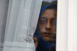 Young South Asian woman looking out of window,