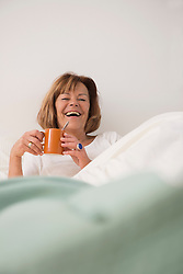 Senior woman at her bedroom drinking tea in the morning, Munich, Bavaria, Germany