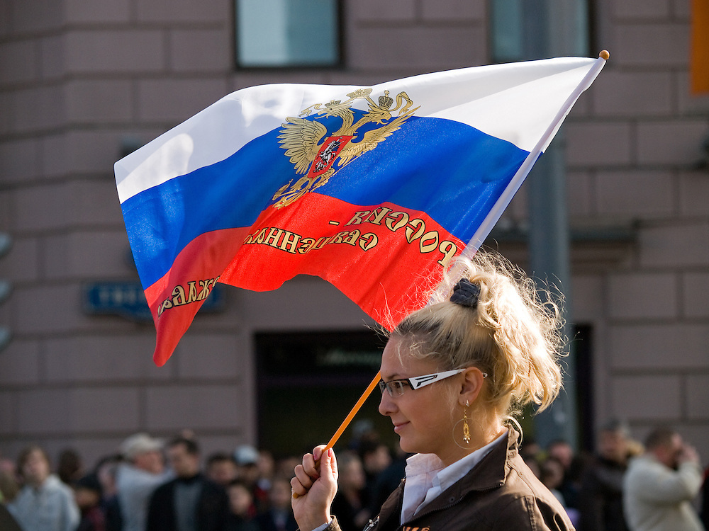 Junge Frau mit der russischen Nationalflagge und dem russischen Wappen im Zentrum vor der größten Militärparade in Rußland seit Ende der Sowjetunion 1991 (9.Mai 2008).<br /> <br /> Young women with the Russian flag shortly before the Victory Day parade (took place the 9th of May 2008) which showcased military hardware for the first time since the Soviet collapse.