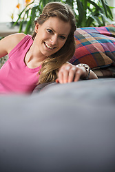 Portrait of a young woman resting in living room, Munich, Bavaria, Germany