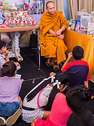 10 JANUARY 2015 - BANGKOK, THAILAND:  A Buddhist monk talks to children in Government House during Children's Day celebrations in Bangkok. National Children's Day falls on the second Saturday of the year. Thai government agencies sponsor child friendly events and the military usually opens army bases to children, who come to play on tanks and artillery pieces. This year Thai Prime Minister General Prayuth Chan-ocha, hosted several events at Government House, the Prime Minister's office.   PHOTO BY JACK KURTZ