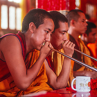 Tibetan Buddhist monks chant and play musical instruments during  a sacred puja ceremony in a monastery in the Kathmandu Valley, Nepal, 1996.