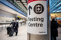 © Licensed to London News Pictures. 15/02/2021. London, UK. Flight crew walk past a Testing Centre Sign at London Heathrow Terminal 5 this morning as hotels near Heathrow start to accept quarantine passengers. From today, (Monday 15 February 2021) anyone arriving from a red-list destination must quarantine at a designated hotel and pay a hotel fee of £1,750 for a 10 day quarantine period. Photo credit: Alex Lentati/LNP