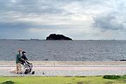 people walking people and dog with Tokyo Bay and Sarushima island in Yokosuka Japan