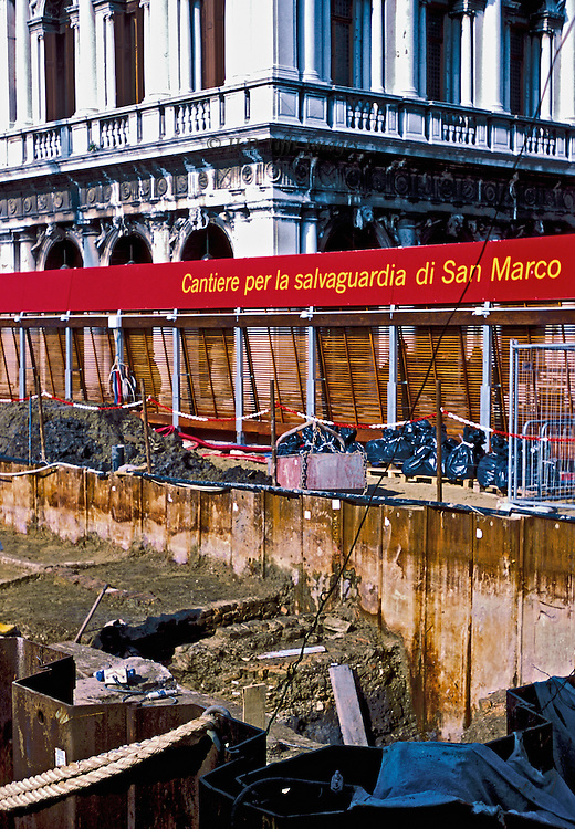 """Tight view of barriers and bulwarks being constructed at the water edge (molo) of the Piazza di San Marco, Venice.  Red banner inscribed: """"Cantiere per la salvaguardia di San Marco"""".  Beyond, a corner of the Biblioteca Sansoviniana."""
