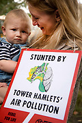 The Air that we Grieve march on July 12th 2019 in East London, United Kingdom. Organised by Extinction Rebellion to draw attention to air pollution and the climate emergency. A mother holds a baby and a placard with a picture of lungs with the words  Stunted by Tower Hamlets air pollution.