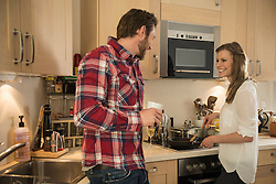 Couple preparing food in the kitchen and smiling, Munich, Bavaria, Germany