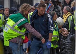 Licensed to London News Pictures. 26/09/2020. London, UK. An injured man get medical help at Trafalgar Square, central London. Protestors demonstrate against lockdown and to stop 5G organised march claiming Covid is a hoax. The 73-year-old meteorologist led more than 10,000 anti-lockdown protesters who believe coronavirus is a hoax at the 'Unite for Freedom'.Photo credit: Marcin Nowak/LNP
