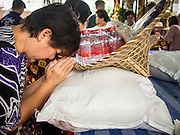 """26 AUGUST 2013 - BANGKOK, THAILAND:     A woman prays over rice she is donating to the Poh Teck Tung Foundation for Hungry Ghost Month in Bangkok. Poh Teck Tung operates hospitals and schools and provides assistance to the poor in Thailand. The seventh lunar month (August - September in 2013) is when the Chinese community believes that hell's gate will open to allow spirits to roam freely in the human world for a month. Many households and temples will hold prayer ceremonies throughout the month-long Hungry Ghost Festival (Phor Thor) to appease the spirits. During the festival, believers will also worship the Tai Su Yeah (King of Hades) in the form of paper effigies which will be """"sent back"""" to hell after the effigies are burnt.    PHOTO BY JACK KURTZ"""