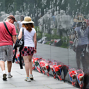 Hundreds of bunches of flowers line the reflecting wall of the Korean War Veterans Memorial on the National Mall in Washington DC. Etched into the wall are thousands of images depicting photos of Americans who died in the war.