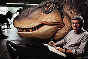George Callison, an expert on dinosaurs, and an artist, sketches and makes notes for upcoming dinosaur models and exhibits in front of a Tyrannosaurus Rex head  at the Dinamation factory in Los Angeles, California. Dinamation International, a California-based company, makes a collection of robotic dinosaurs. The dinosaurs are sent out in traveling displays to museums around the world. The dinosaur's robotic metal skeleton is covered by rigid fiberglass plates, over which is laid a flexible skin of urethane foam. The creature's joints are operated by compressed air and the movements controlled by computer.