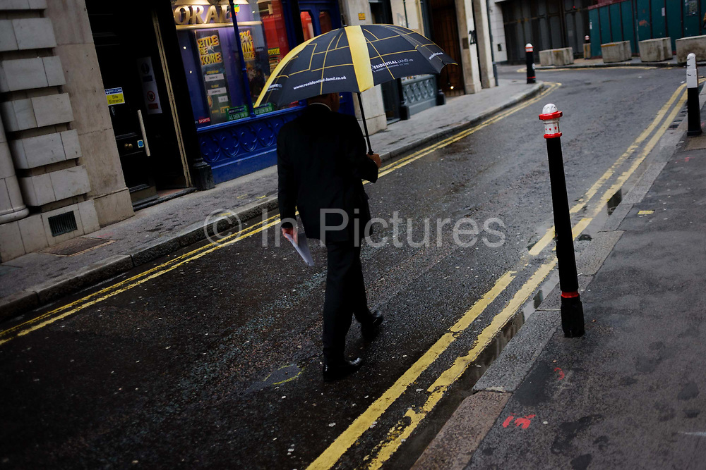 A businessman walks down a quiet financial district back street carrying an umbrella whose stripes echo those of double-yellow lines. This coincidental theme of yellows and lines make for a slightly comical landscape. Rainfall is making the capital's pavements glisten with narrow puddles in the gutter. The man strides down the street in London's financial district, more specifically where insurance brokers operate near Lloyds of London.