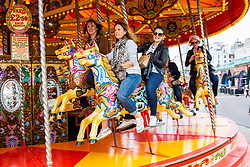 © Licensed to London News Pictures. 18/05/2019. Brighton, UK.  Members of the public take a ride on the Brighton and Hove seafront carrousel as milder weather is hitting the South coast. Photo credit: Hugo Michiels/LNP