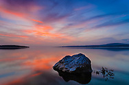 Stone in a calm lake at sunset