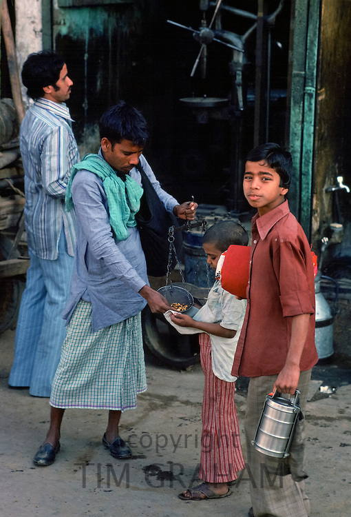 Indian man weighing out food for children doing food shopping