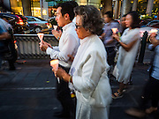 24 AUGUST 2015 - BANGKOK, THAILAND: People walk with lit candles to a memorial service for victims of the Erawan Shrine bombing. One week after the a bomb at the Erawan Shrine in the center of Bangkok killed dozens and hospitalized scores of people, police have not made any arrests. Police bomb sniffing dogs have been deployed to malls and markets around Bangkok. There was a large memorial service sponsored by businesses close the bomb site Monday evening.      PHOTO BY JACK KURTZ